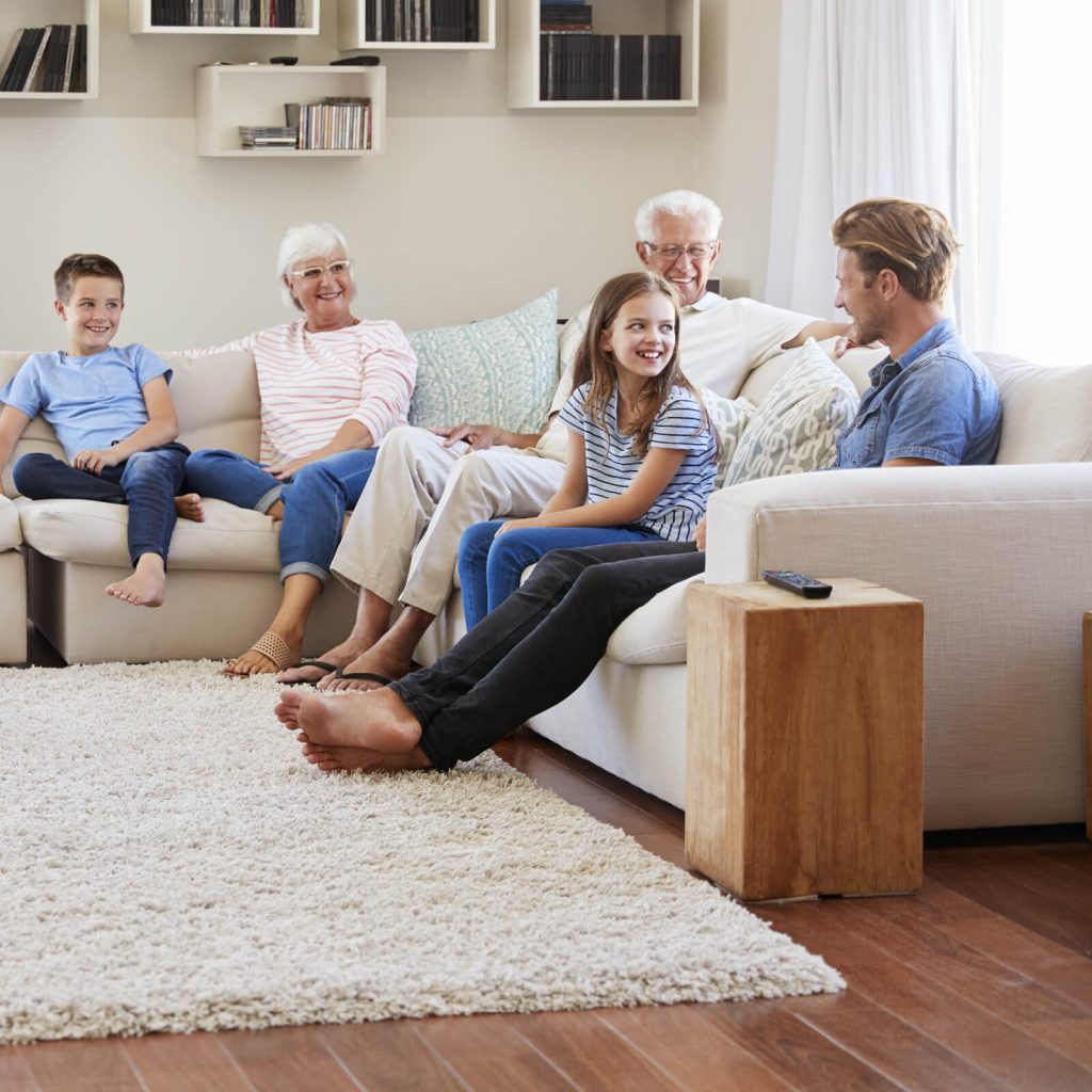 Family gosping sitting on sofa | McCool's Flooring